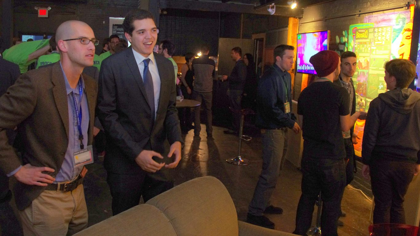 2 men in suits playing a video game and smiling