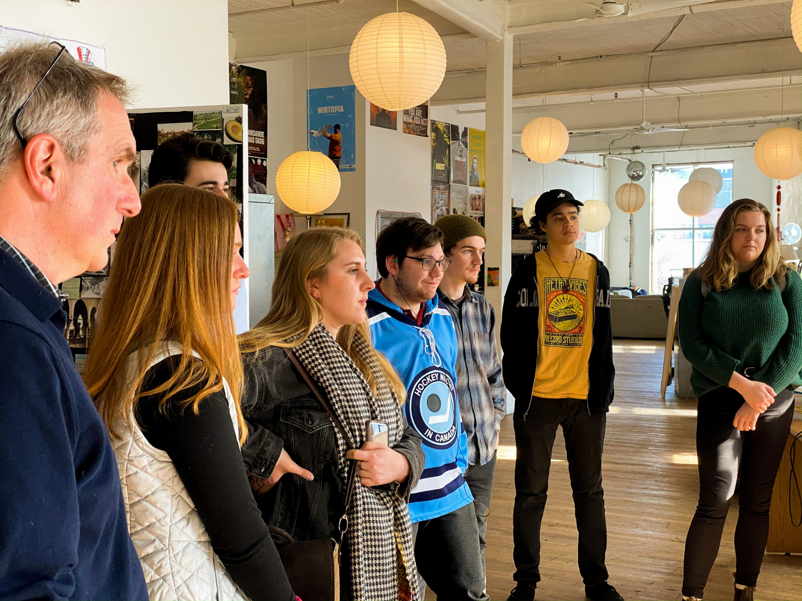 Group of students and faculty listening to a presenter off-screen