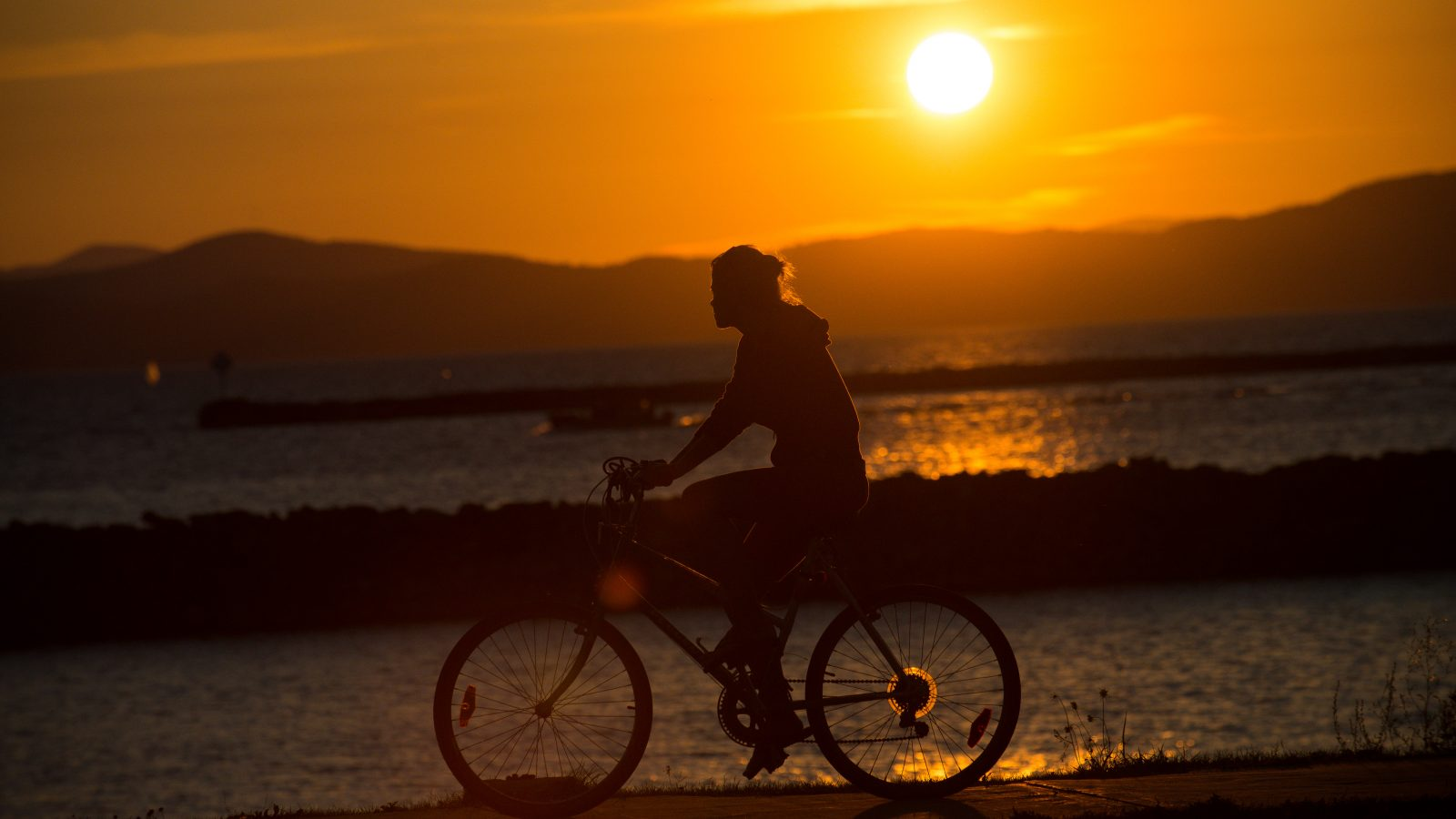 Man biking with mountains and Lake Champlain in the background