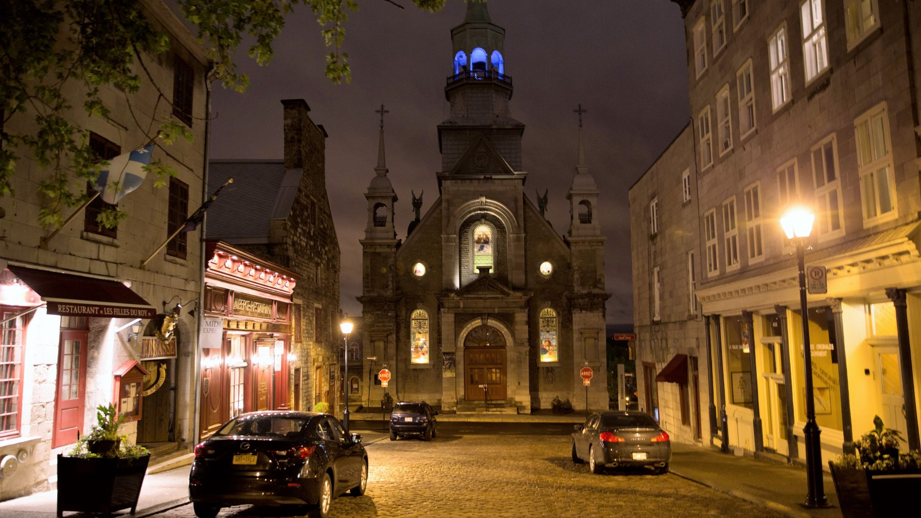 Street of cars and shops at night with a church at the end of the street, at dusk