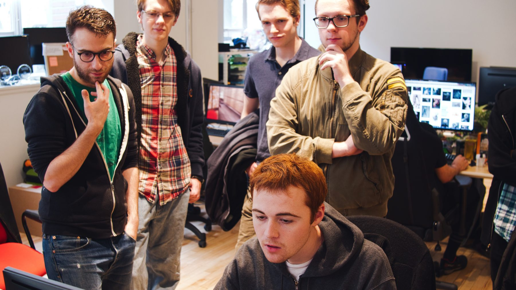 Group of students looking thoughtfully at a computer screen