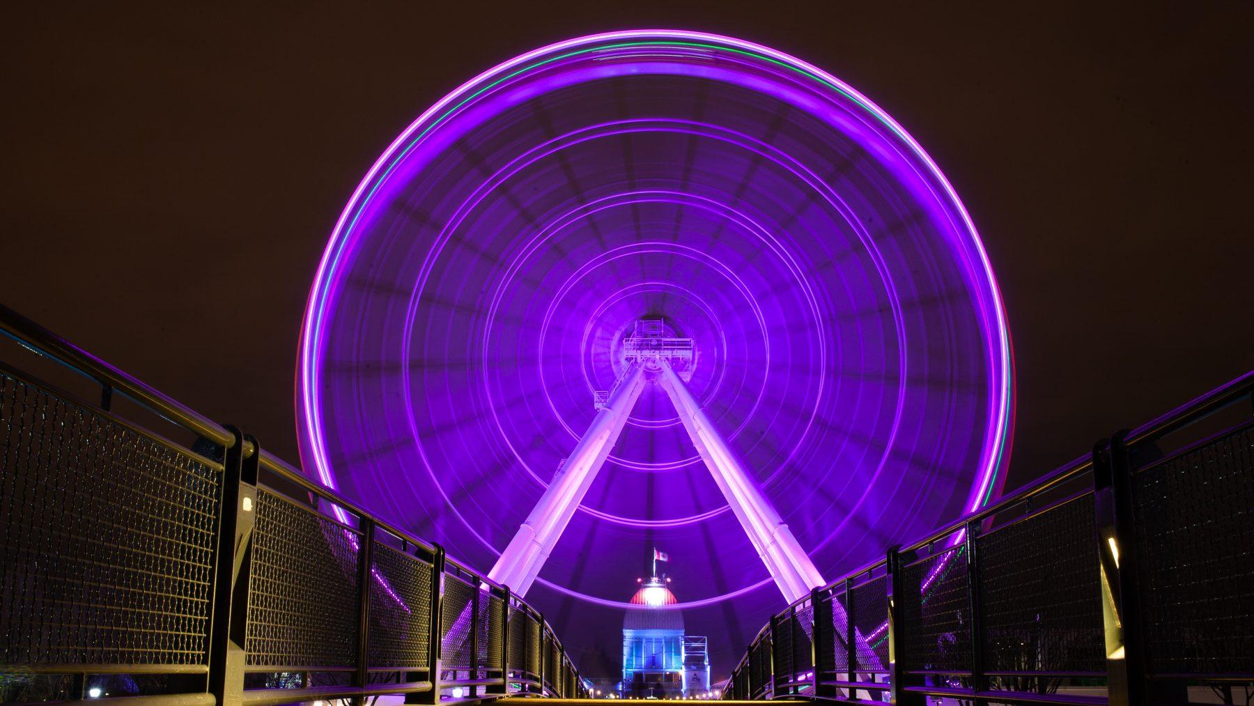 Motion blur shot of a ferris wheel lit up with purple lights