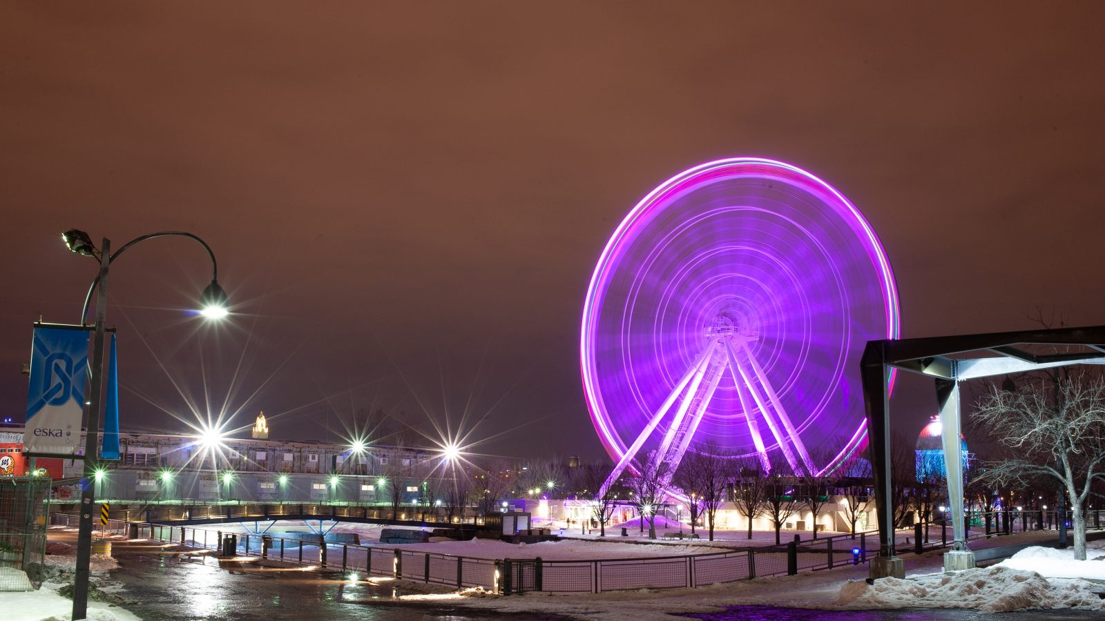 Motion blur shot of a ferris wheel lit up with purple lights and Montreal in background