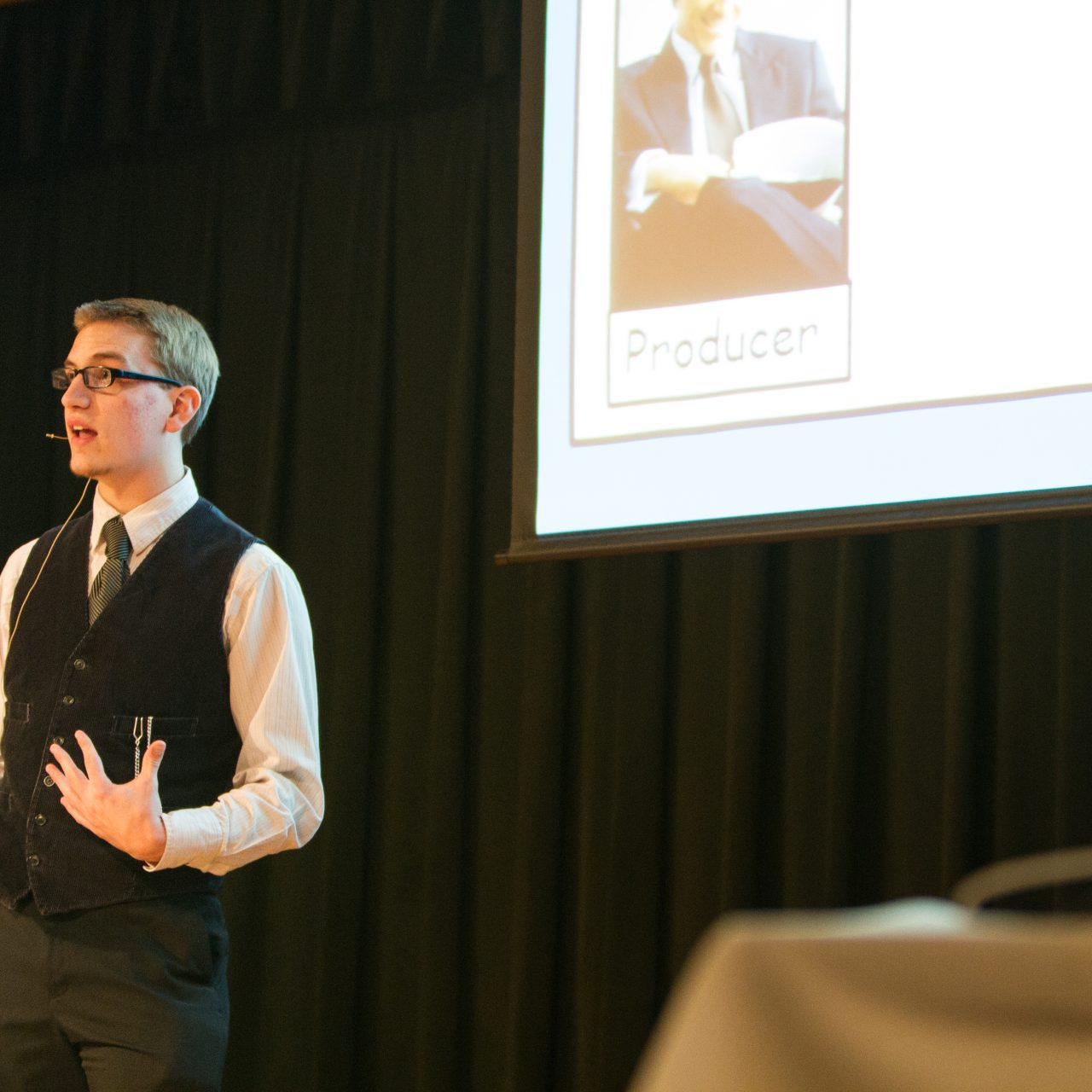 Student presenting a game on stage with a projected screen behind him