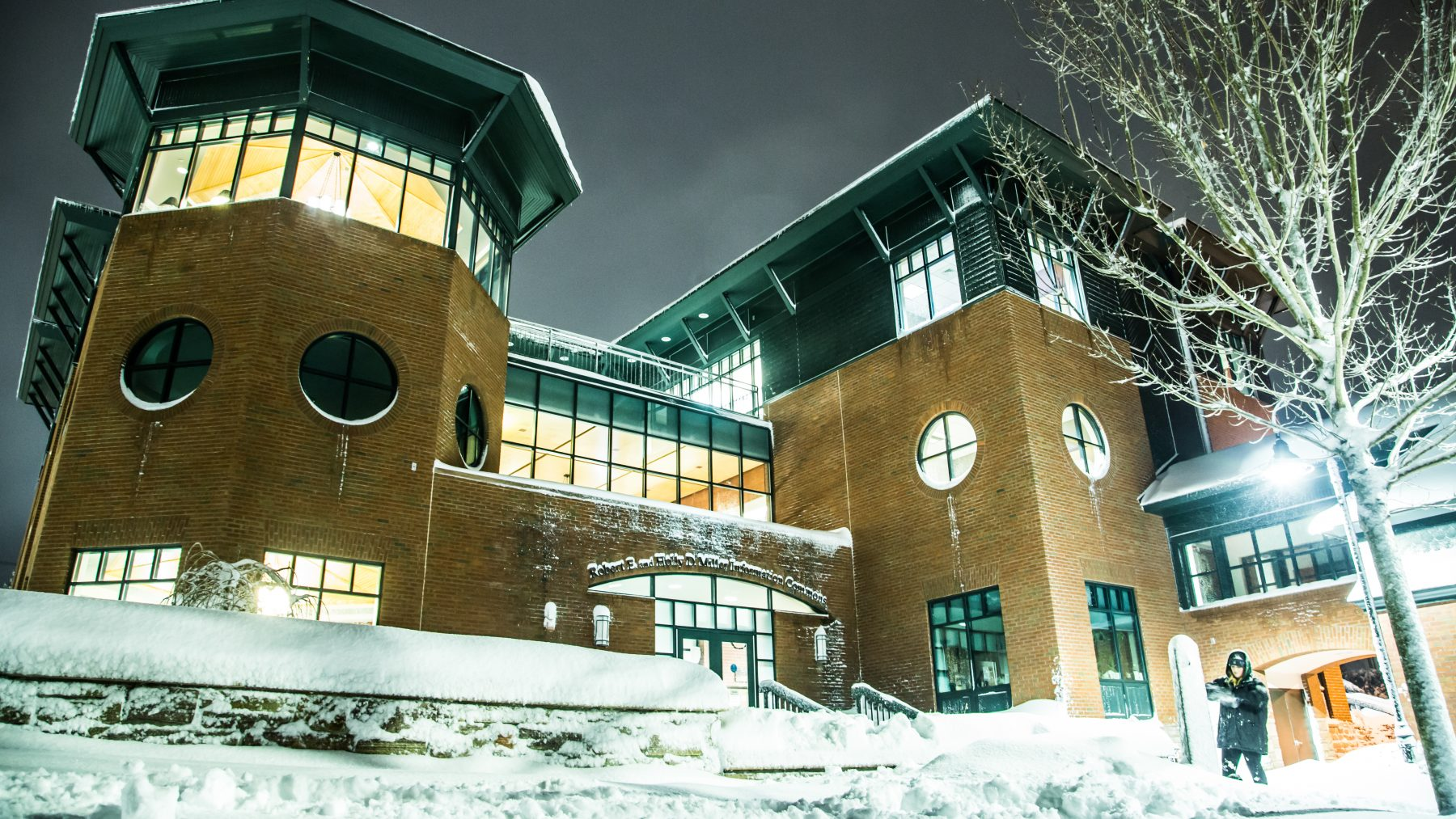 Champlain campus building with lights on and covered in snow