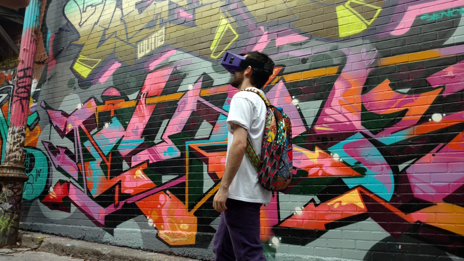 Student wearing VR headset in front of graffiti art on a brick wall