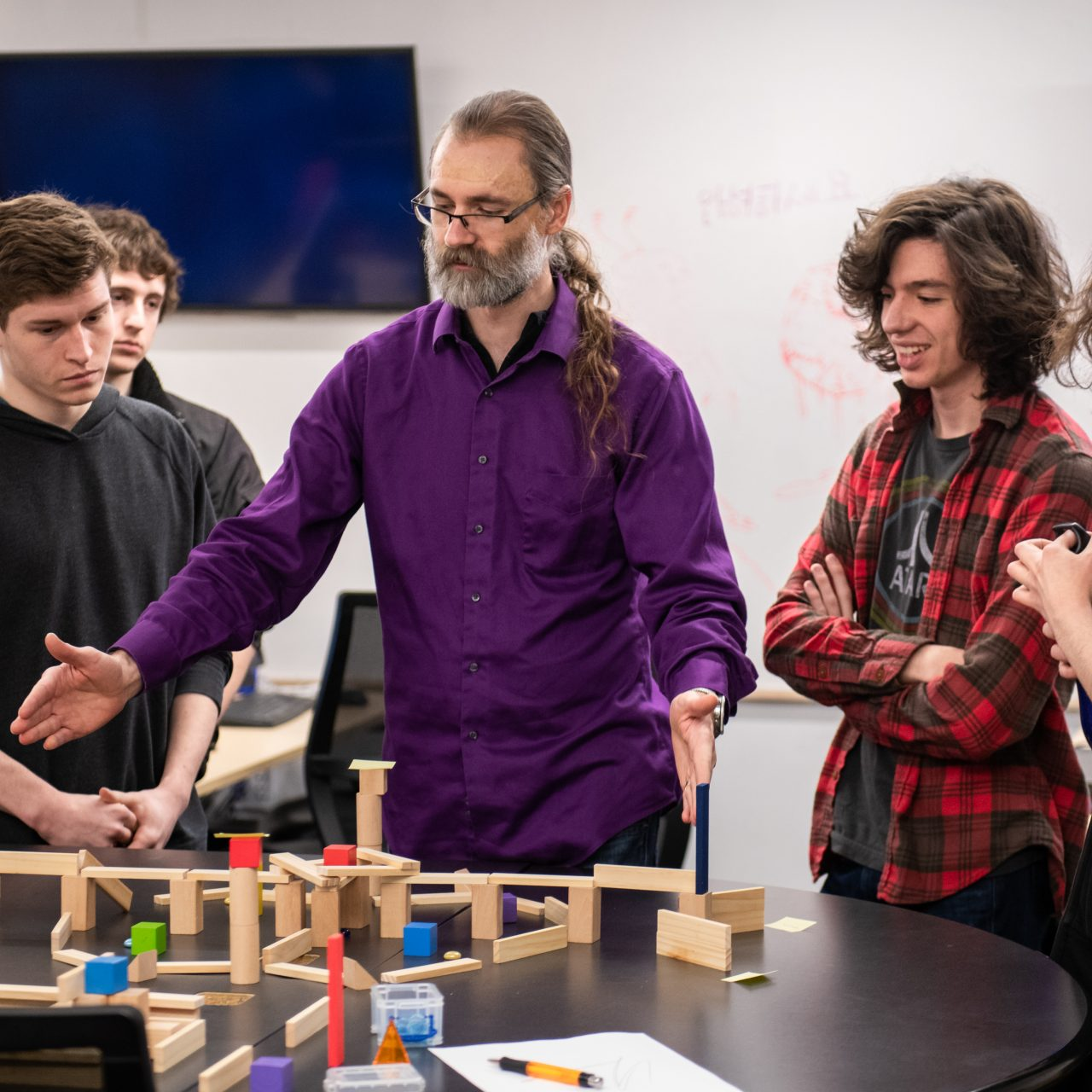 3 students responding to a professor who is gesturing towards blocks on a table