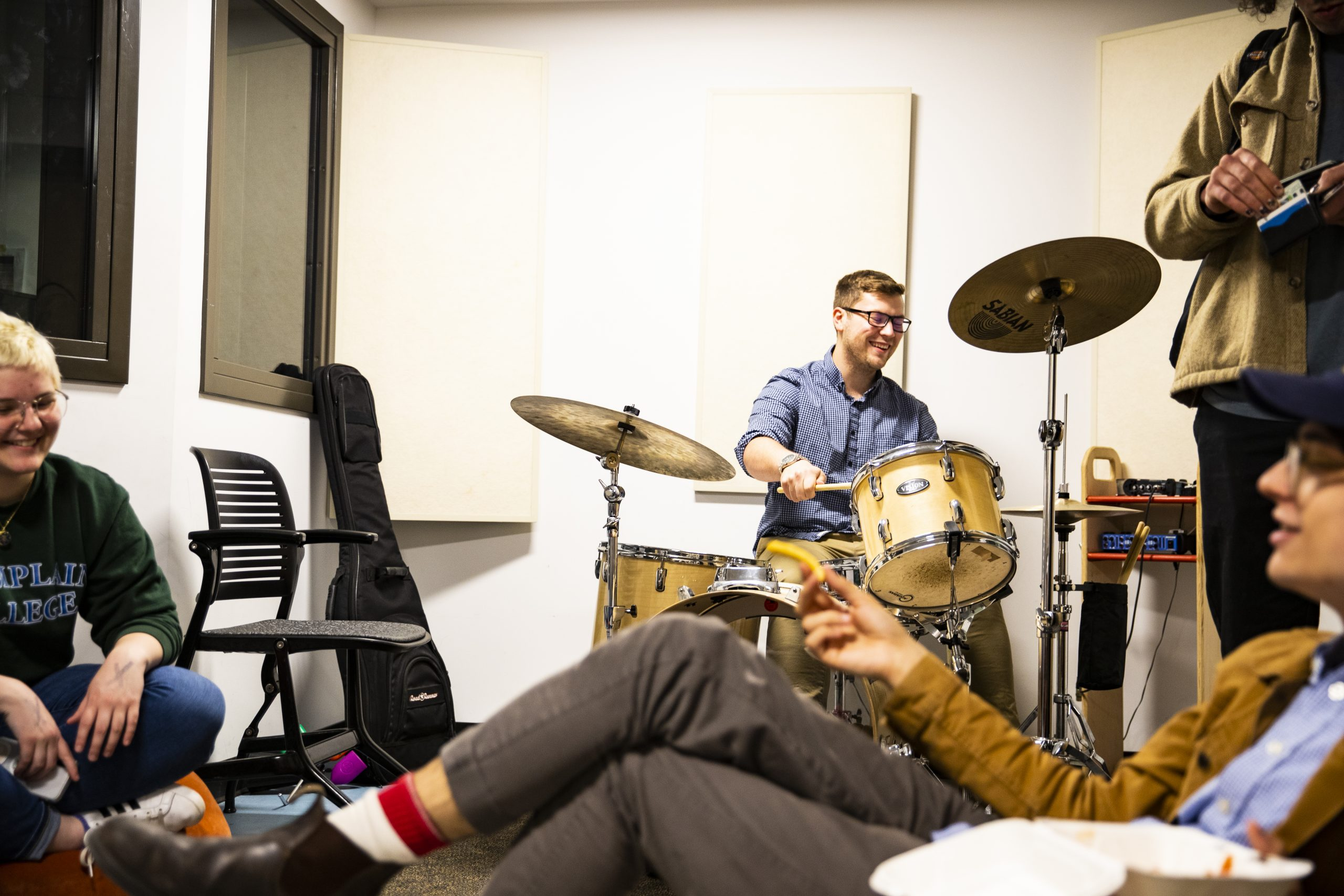 Group of students in a room playing drums and sitting on couches