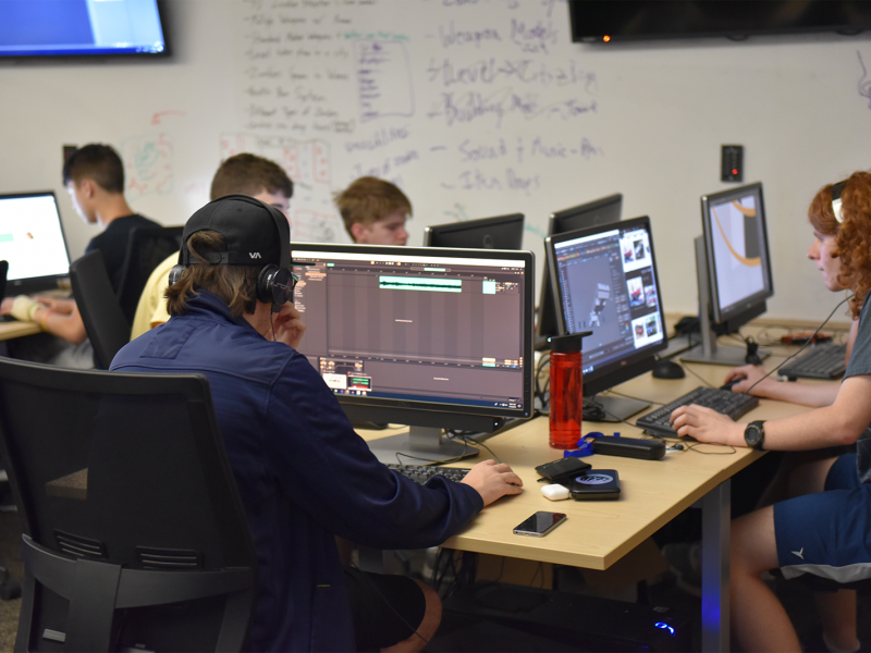 Group of young students around a large desk, looking at computer screens, working on game projects