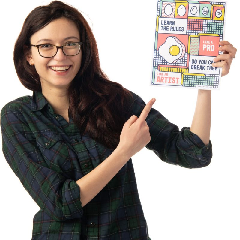 Profile image of a smiling student pointing at a book