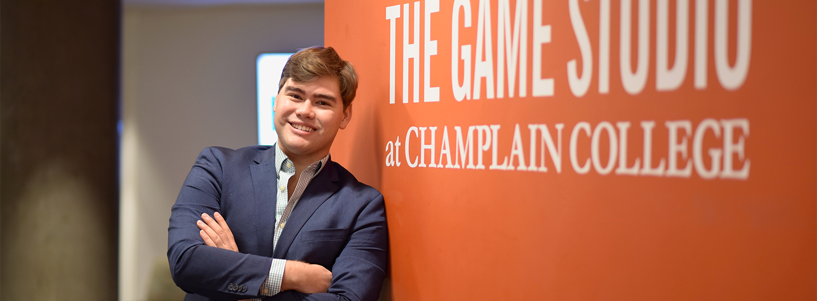 Smiling student in a suit leaning on an orange wall