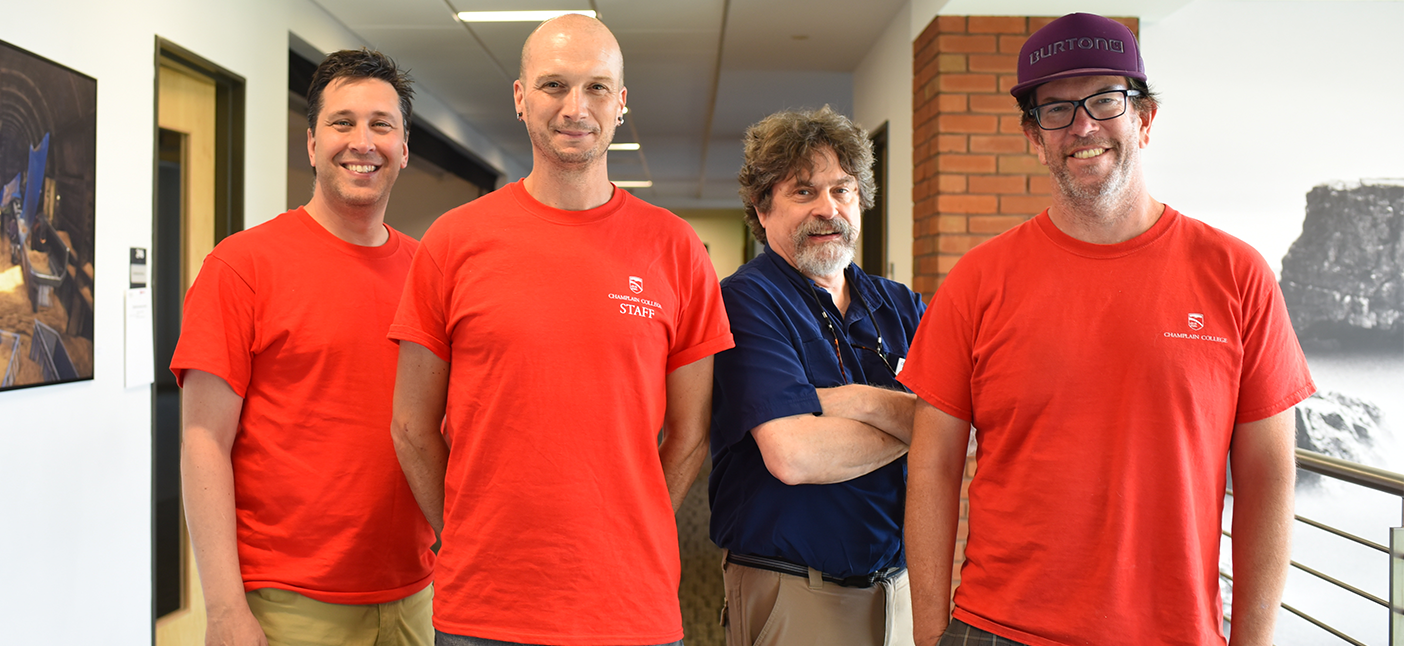 4 professors smiling in a hallway