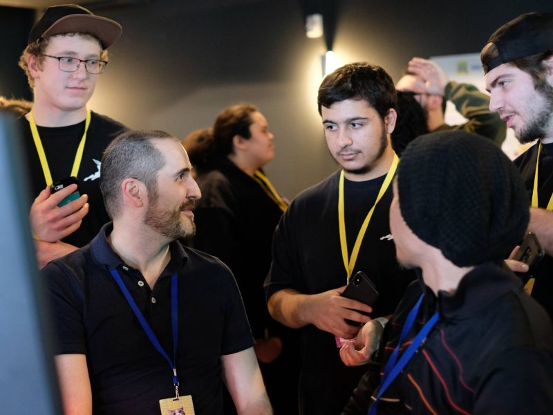 Faculty working with students at a game event