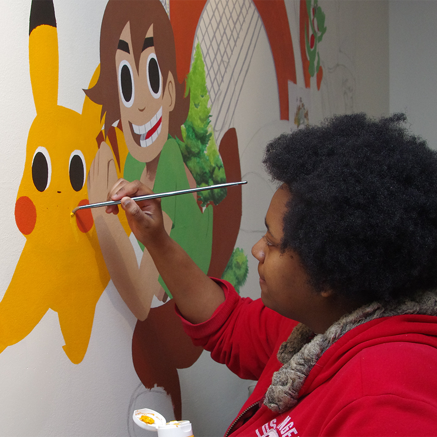 Student painting cartoons on a wall