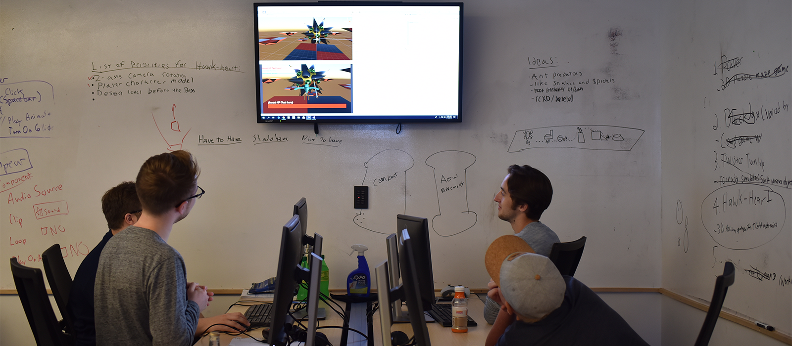 Students looking up at a screen showing video game assets